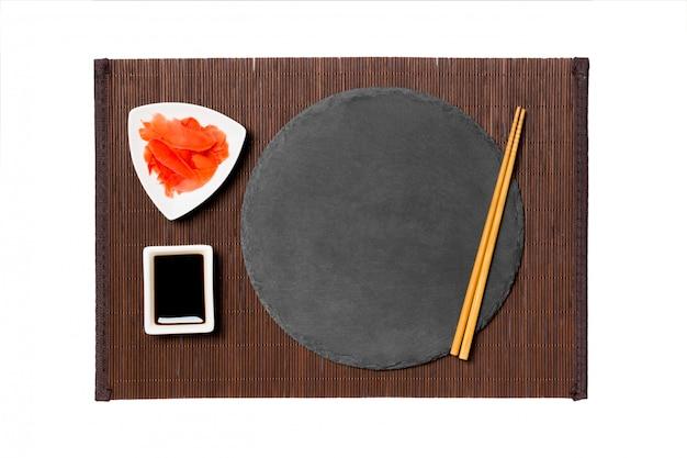 Placa de ardósia preta emptyround com pauzinhos para molho de sushi, gengibre e soja na esteira de bambu escuro. vista superior com copyspace