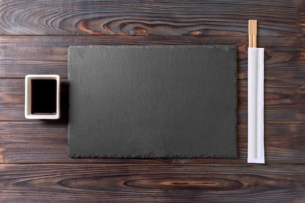 Placa de ardósia preta retangular vazia com pauzinhos para sushi e molho de soja na madeira