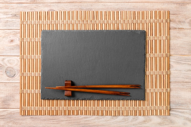 Placa de ardósia preta retangular vazia com pauzinhos para sushi na madeira