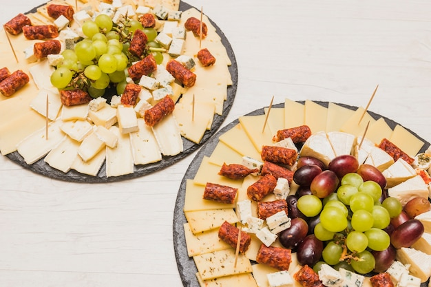 Placa de ardósia preta servindo com prato de queijo na mesa de madeira
