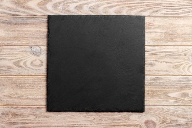 Placa de ardósia sobre fundo de madeira velha com espaço de cópia