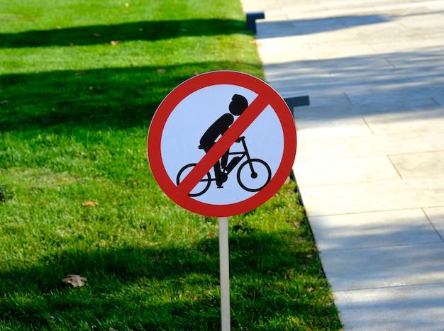 Placa de bicicleta proibida no poste de madeira na entrada do parque.