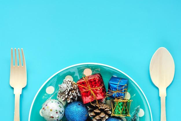 Placa de bolinhas de enfeites de natal com colher e garfo em fundo azul para o dia de natal