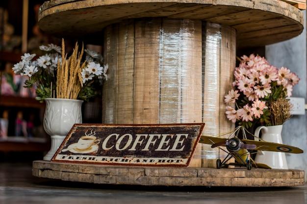 Placa de café, helicóptero de brinquedo e flores falsas em um vaso que é exibido em uma mesa de madeira.