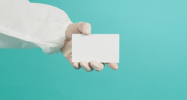 Placa de cartão branca em branco na mão. com terno ppe e luva de látex em verde hortelã ou fundo azul tiffany.