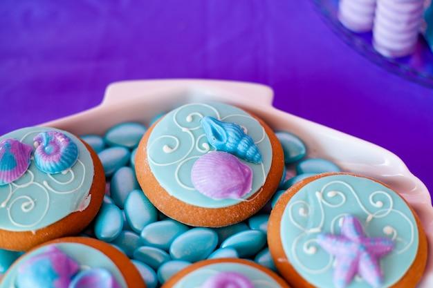 Placa de casca branca cheia de bombons de chocolate com cobertura azul, biscoitos com conchas, estrelas na mesa