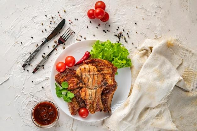 Placa de cerâmica branca com carne de porco grelhada, folhas de alface, tomate e pimenta vermelha e molho nas tigelas