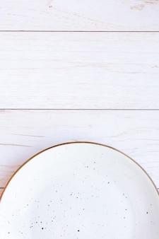 Placa de cerâmica branca na superfície de madeira, vista superior