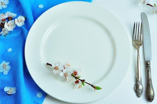 Placa de cerâmica branca vazia com ferro vintage talheres