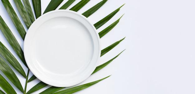 Placa de cerâmica branca vazia em folhas de palmeira tropical em branco
