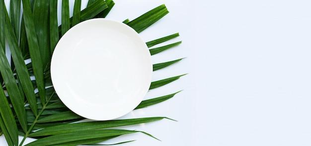 Placa de cerâmica branca vazia em folhas de palmeira tropical em fundo branco. vista do topo