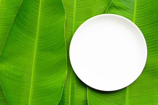 Placa de cerâmica branca vazia em fundo de folhas de bananeira. vista do topo