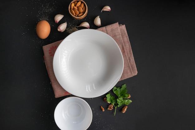 Placa de cerâmica branca vazia na mesa preta, ingredientes frescos para cozinhar, pimenta, utensílios de mesa