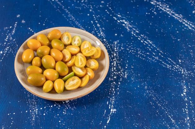 Placa de cerâmica com fatias de frutas frescas de kumquat na superfície de mármore.