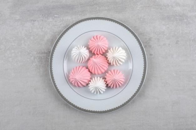 Placa de cerâmica de doces de merengue branco e rosa na superfície da pedra.