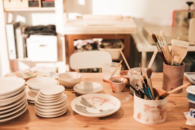 Placa de cerâmica e tigela com pincéis e ferramentas na mesa de madeira na oficina