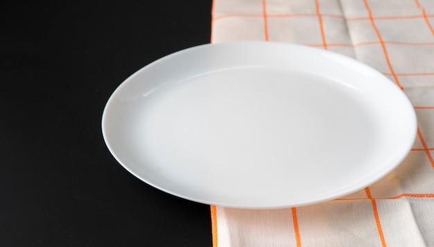 Placa de cerâmica limpa vazia ou prato em uma superfície de concreto