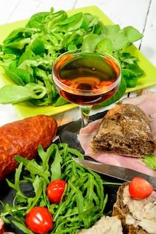 Placa de charcutaria com copo de vinho