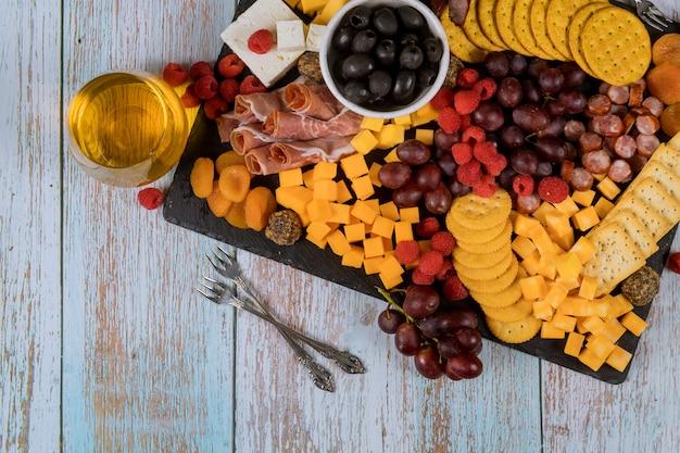 Placa de charcutaria com queijo, uva, framboesa, bolachas e bebidas