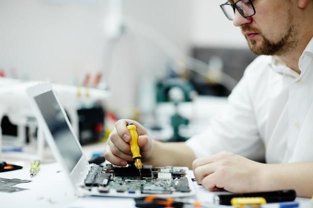 Placa de circuito de montagem do homem no laptop