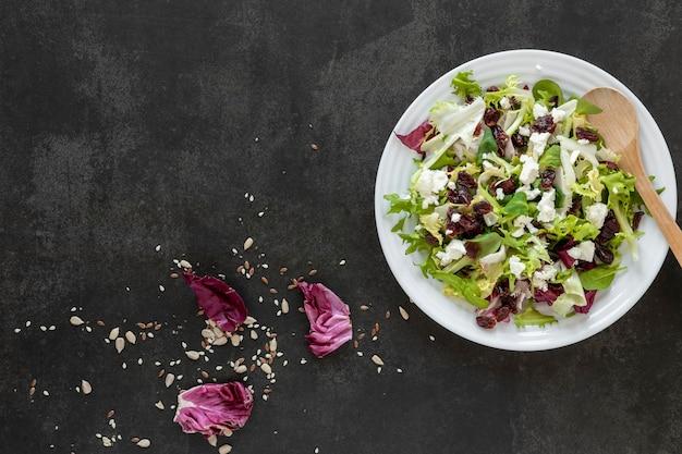 Placa de cópia-espaço com salada na mesa