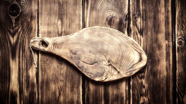 Placa de corte antiga com espaço vazio para texto na mesa de madeira.