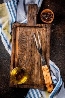 Placa de corte antiga com garfo, ervas e especiarias