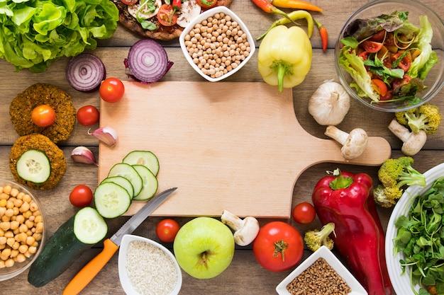 Placa de corte cercada por legumes
