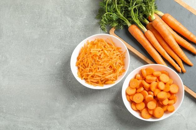 Placa de corte com cenouras maduras na mesa cinza, espaço para texto