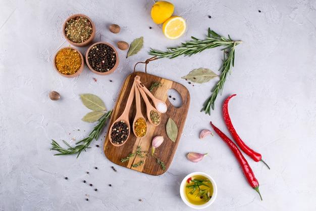 Placa de corte com ervas e especiarias - alecrim, alho, sal, pimenta, azeite, limão. fundo culinário. comida plana leigos.