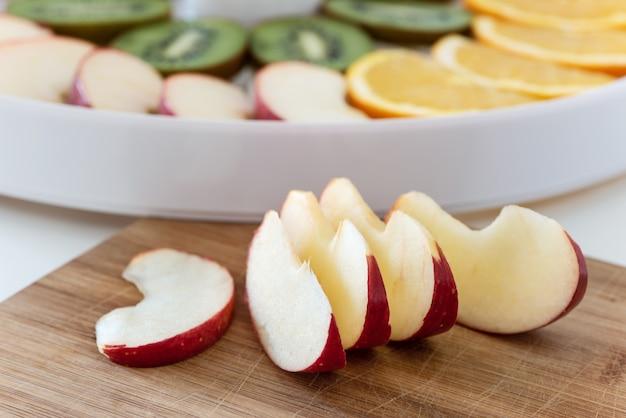 Placa de corte com fatias de maçã. atrás está um desidratador com rodelas de laranja, kiwi e maçãs.