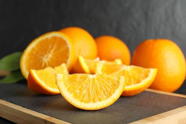 Placa de corte com pedaços de laranja contra fundo preto, closeup