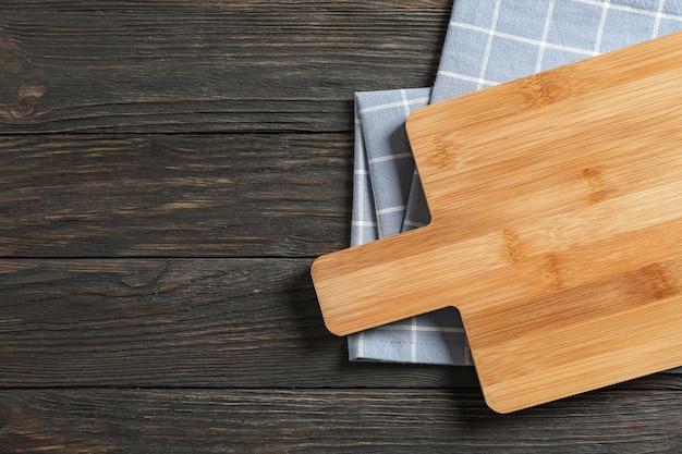 Placa de corte com toalha de cozinha em fundo de madeira, espaço para texto