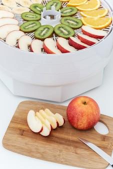 Placa de corte com uma faca e pedaços de maçã. atrás está um desidratador com rodelas de laranja, kiwi e maçãs.