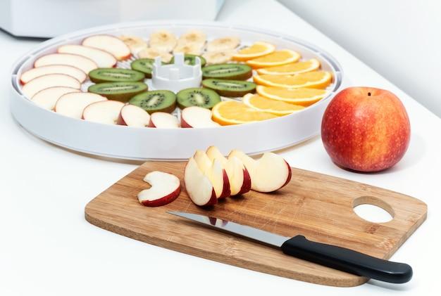 Placa de corte com uma faca e pedaços de maçãs. atrás está uma bandeja de desidratador com fatias de laranja, kiwi e maçãs.