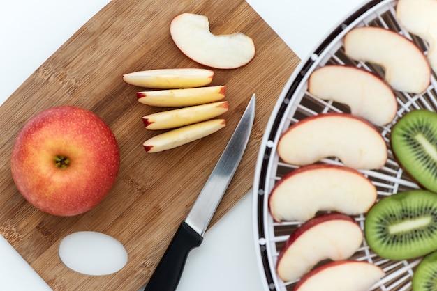 Placa de corte com uma faca e pedaços de maçãs. perto está um desidratador com rodelas de laranja, kiwi e maçãs.