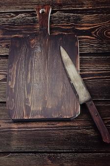 Placa de corte com uma faca em um fundo de madeira velho