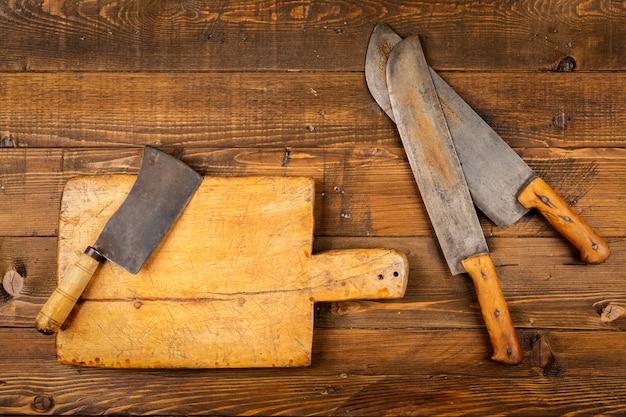 Placa de corte com velhas facas de cozinha na mesa de madeira