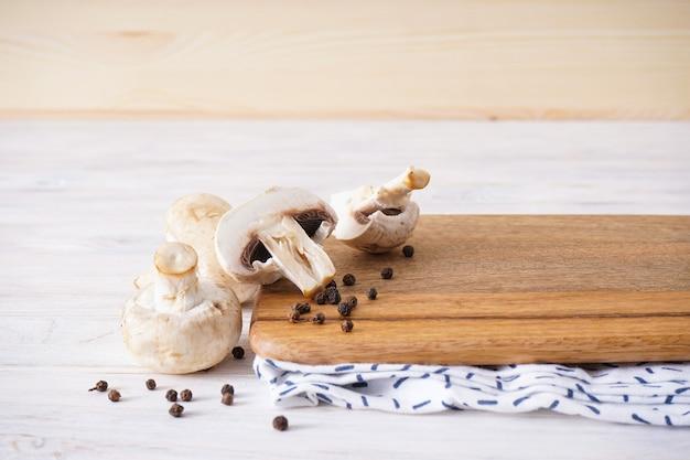 Placa de corte de madeira e cogumelos em um fundo de madeira, lugar para texto.