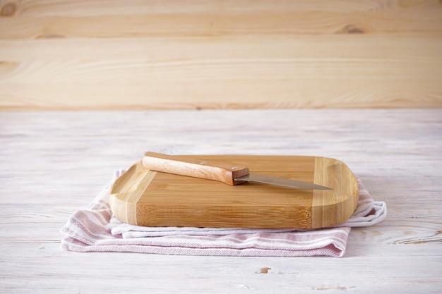 Placa de corte de madeira e faca em um fundo de madeira, espaço para texto.