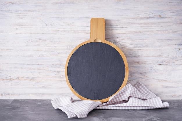 Placa de corte de madeira e toalha de cozinha na mesa de madeira, espaço para texto.