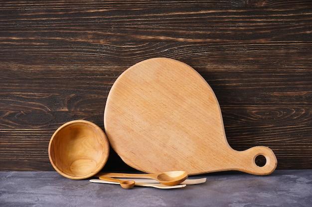 Placa de corte de madeira e utensílios de cozinha em um fundo de madeira, lugar para texto.