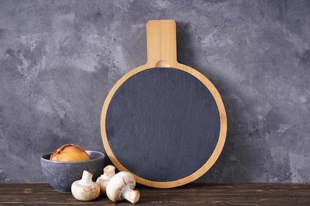 Placa de corte de madeira e vegetais em um fundo cinza, espaço para texto.