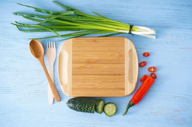 Placa de corte de madeira e vegetais na mesa de madeira, espaço para texto. postura plana.