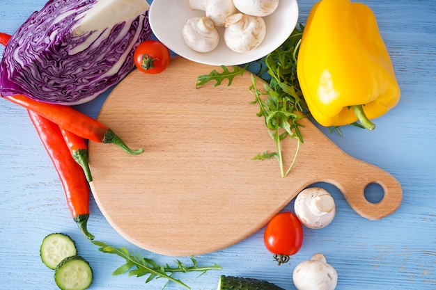 Placa de corte de madeira e vegetais na mesa de madeira, lugar para texto, close-up.