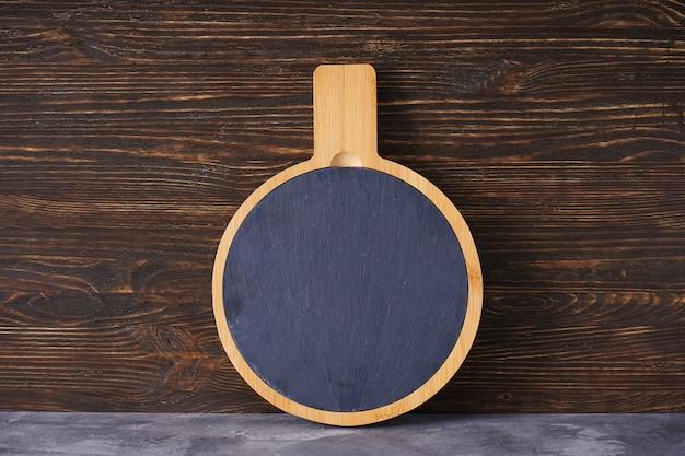 Placa de corte de madeira em um fundo de madeira, espaço para texto.