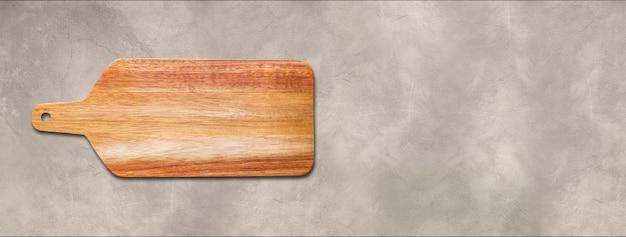 Placa de corte de madeira isolada em fundo de concreto. banner panorâmico horizontal
