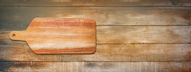 Placa de corte de madeira isolada em fundo de madeira velho. banner panorâmico horizontal