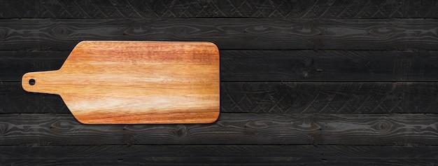 Placa de corte de madeira isolada em fundo preto de madeira. banner panorâmico horizontal