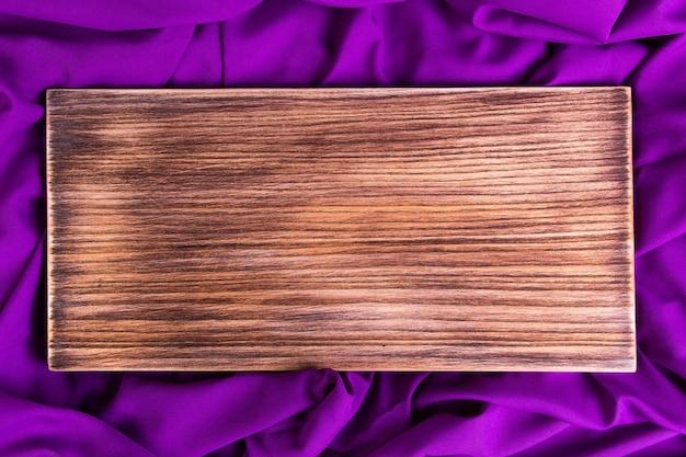 Placa de corte de madeira no pano roxo, violeta do guardanapo.